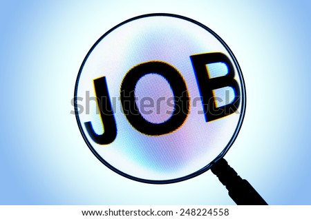 Looking for job using magnifying glass over computer screen - stock photo