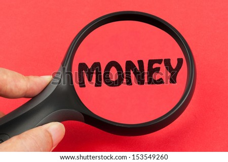Looking for money using a magnifier on hand - stock photo