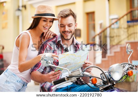 Looking for place to go. Beautiful young loving couple sitting on scooter together and examining map while woman pointing it and smiling - stock photo