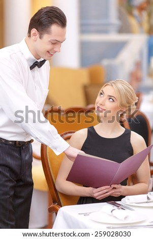 Looking for something special. Beautiful young woman looking waiter pointing at menu and smiling while sitting at the restaurant - stock photo