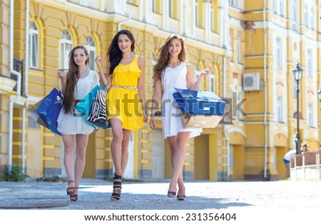 Looking for the best shopping offer. Three positive and pretty young girls are going forward in a good mood. Shopping with a smile - stock photo