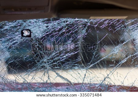 Looking from the inside through the broken windshield of a car accident, which was parked in front. - stock photo