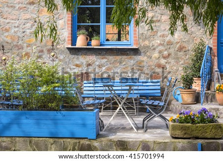 Beautiful Looking In A Very Idyllic Courtyard, With An Old Field Stone Barn, Blue  Painted