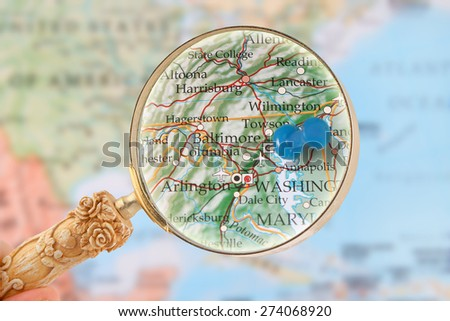 Looking in on Baltimore, Maryland, USA through a magnifying glass with blurred map in the background - stock photo