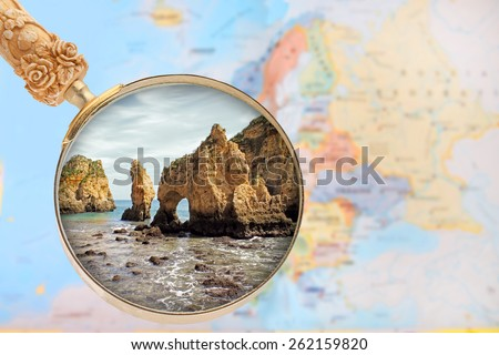 Looking in on Ponte da Piedade in  Portugal with a magnifying glass or loop with European map in the background - stock photo