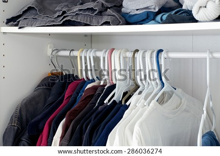 Looking inside a man's closet or armoire full of clothes hanging on hangers.