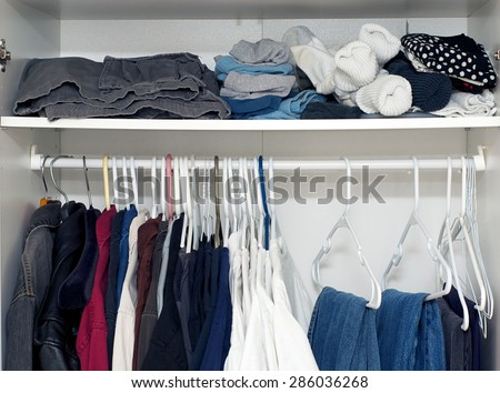 Looking inside a man's closet or armoire full of clothes hanging on hangers and laying on shelf.