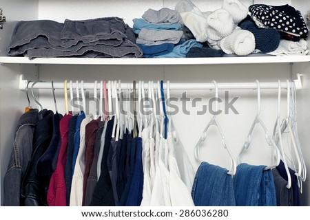 Looking inside a man's closet or armoire full of clothes hanging on hangers and laying on shelf. - stock photo