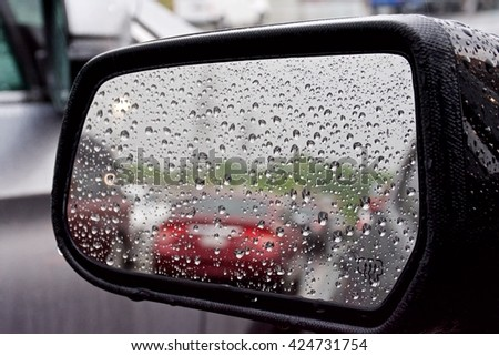 Looking into a car side mirror on a rainy day