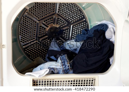 Looking into a front loading clothes dryer with dried laundry. - stock photo