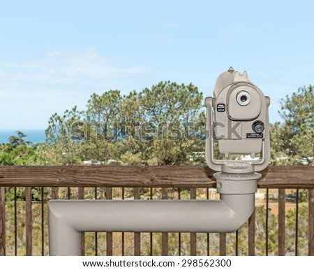 Looking into the distance with coin operated telescope. View of distant trees in rural area. Blue sky background. Copy space.   - stock photo
