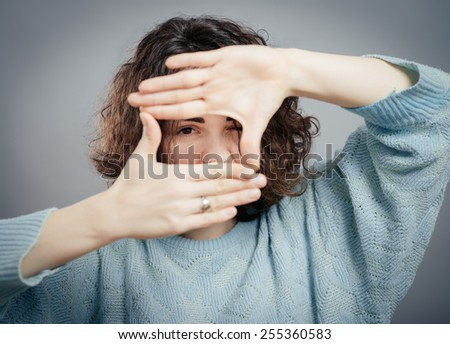 Looking of happy woman through frame of fingers
