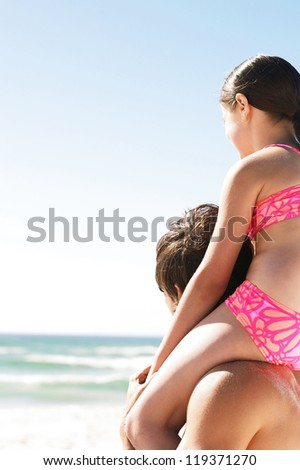 Looking out at the surf from a high perch on her fathers shoulders. A little girl has fun with the family - stock photo