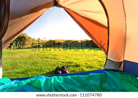 Looking out of open tent door upon green meadow and forest in morning sunshine - stock photo