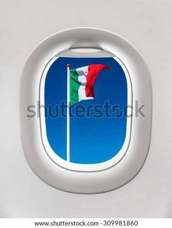 Looking out the window of a plane to the flag of Italy, travel concept - stock photo
