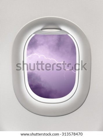 Looking out the window of a plane to the lightning storm, bad weather, turbulence - stock photo