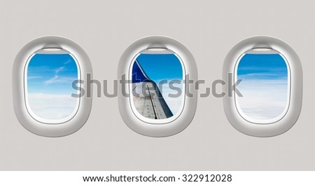 Looking out the windows of a plane to the aircraft wing, blue sky and clouds - stock photo