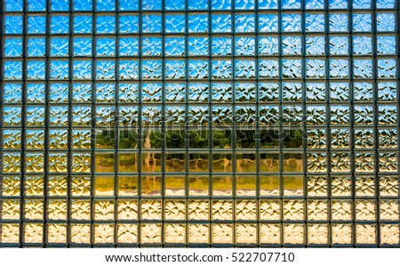 Looking out through a large glass block window with a semi-smooth center section