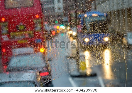 Looking out through rain-specked window to red Double-Decker Bus - stock photo