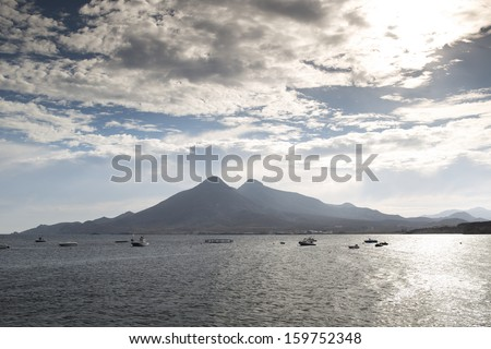 looking out to sea with mountains in the background on a moody cloudy day, cabo de gata, spain - stock photo
