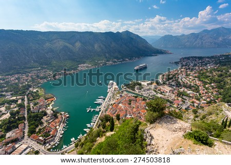 Looking over the Bay of Kotor in Montenegro with view of mountains, boats and old houses with red tile roofs - stock photo
