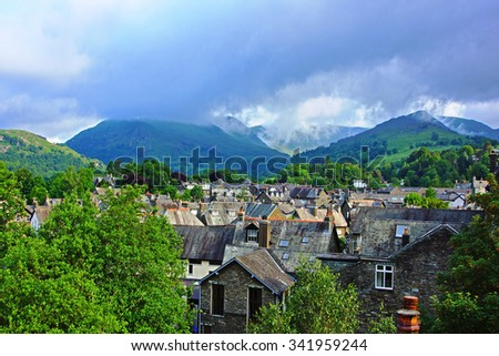 Looking over the roof tops of the town of Ambleside towards the start of the mountain range called The Langdale Pikes, The Lake District, Cumbria, England, United Kingdom - stock photo
