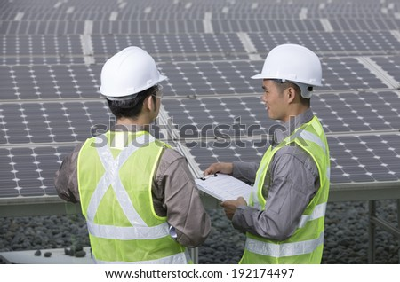 looking over the shoulder of two Chinese maintenance engineers discussing solar panels.