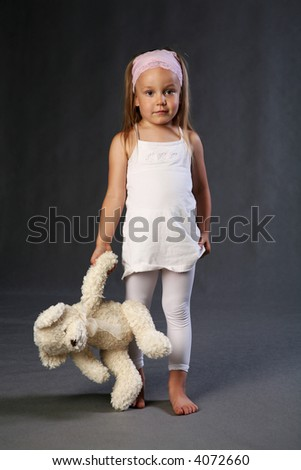 Looking sad and lonely preschool child holding teddybear in hand.