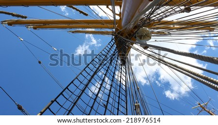 Looking straight up a tall sailing ships mast from below towards the sky. - stock photo
