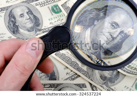 Looking through a magnifying glass to hundred dollars note. Shallow DOF. - stock photo