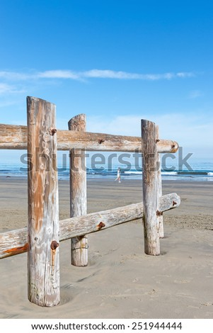 Looking through a wood post fence by the ocean. Rough texture tree trunks form a barrier in the sand. Person running along the shore in blurred background.  - stock photo