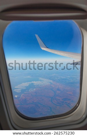 Looking through airplane window during flight - wing with a nice blue sky, land and rivers - stock photo