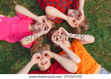 Looking through binoculars. Vivacious friends lying on the floor and smiling while keeping their hands on faces.