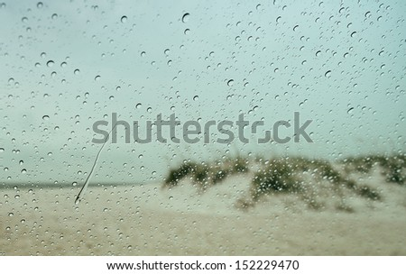 Looking through car windshield with raindrops and rain running down the glass. Beyond is a blurry view of the beach