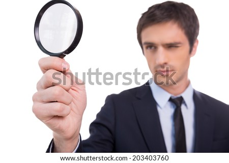 Looking through magnifying glass. Concentrated young man in formalwear looking through a magnifying glass while standing isolated on white background  - stock photo
