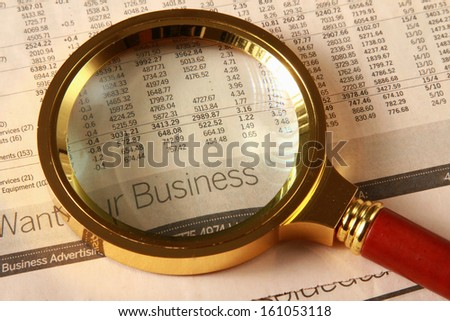 Looking through magnifying glass to financial report