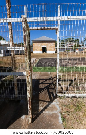 Looking through the fence at the historic Old Fannie Bay Gaol, operated as Her Majesty's Goal and Labour Prison, Darwin with the sandstone infirmary containing the gallows in the background