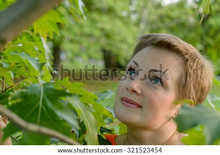Looking through the leaves of a young woman with bright blue eyes.