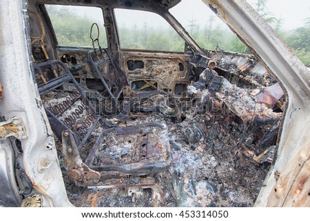 Looking through the open door of a burnt out truck left abandoned on common ground.