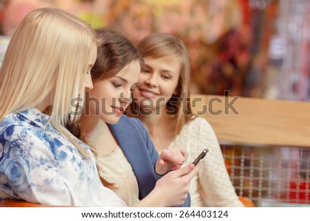 Looking through the pictures. Close-up of three beautiful young women looking at the screen of the smartphone - stock photo