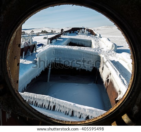 Looking through the window of the old frozen ship, lake Baikal