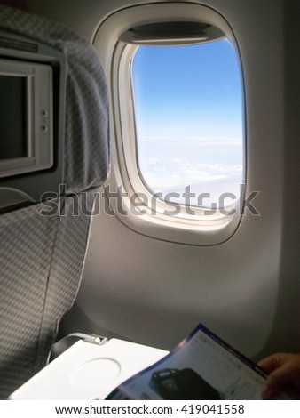 Looking through window aircraft during flight in wing with a nice blue sky - stock photo