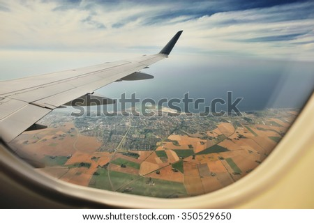 Looking through window aircraft, landing to Copenhagen airport Kastrup. High-angle view from airplane.