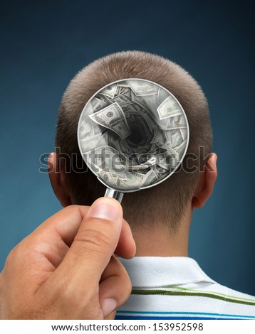 Looking to a mans head thinking about money through magnifying glass - stock photo
