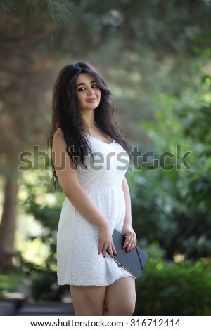 Looking to camera student girl with exercise book, notebooks on hand, 18 years dreaming student girl outdoors, beautiful student girl, young beautiful model, teen, young, Eighteen years  - stock photo