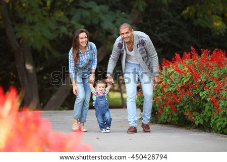 Looking to camera young family walking, teaching to baby - stock photo