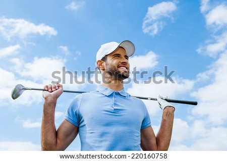 Looking towards success. Low angle view of young happy golfer holding driver and smiling with blue sky as background - stock photo