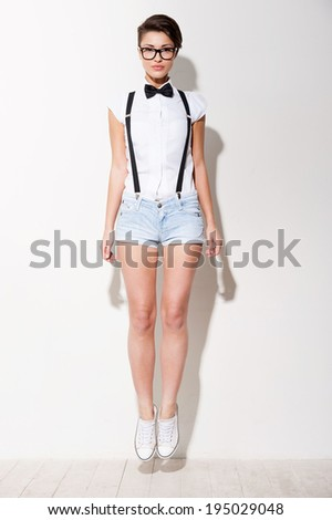 Looking trendy. Full length of beautiful young short hair woman in white shirt and suspenders jumping - stock photo