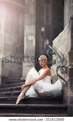 Looking unprotected. Young attractive ballet dancer sitting on the stairs embracing her knees soft focus - stock photo