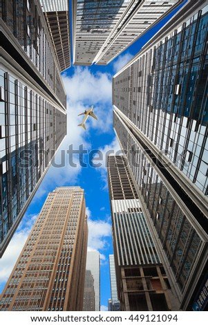 Looking up Aircraft flying over the modern city skyscraper buildings backgrounds